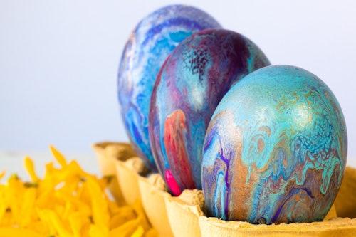 Drei bunt gefärbte Eier mit Mustern stehen in einem Eierkarton.