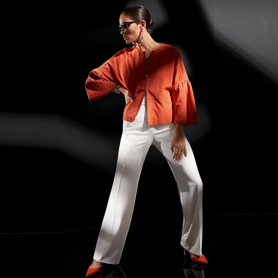 Dame mit Sonnenbrille und Pferdeschwanz trägt Kombination aus Weiß und Orange.