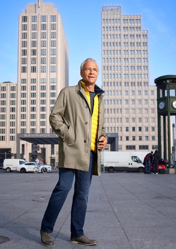 Ein Mann mit beigem Mantel steht vor zwei Hochhäusern, über ihm sieht man blauen Himmel.