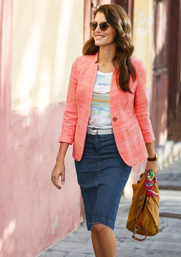 Frau mit Sonnenbrille trägt einen orangenen Blazer, T-Shirt und einen Jeansrock. In der Hand hält sie eine braune Tasche.