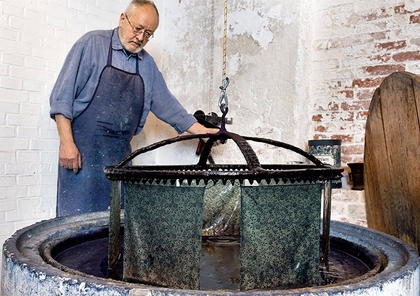 Mann mit blauer Schürze und Hemd steht vor einem Bottich und zieht Stoff aus Wasser.