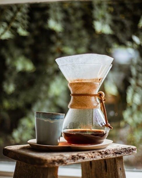 Vastakeitettyä kahvia lasisessa V60-kahvinkeittimessä, joka on puisella penkillä käsinvaletun kupin vieressä.