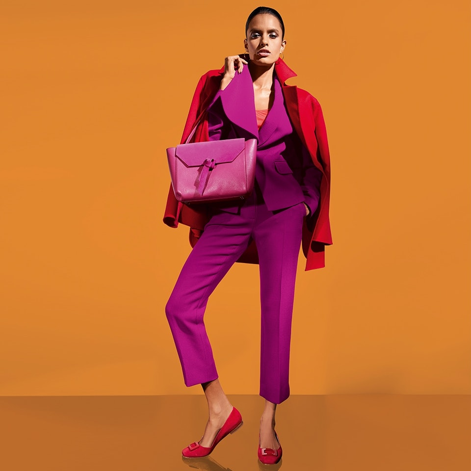 Frau gekleidet in einer Kombination aus Pink und Rot mit Blazer, Bügelfaltenhose und passender Handtasche.