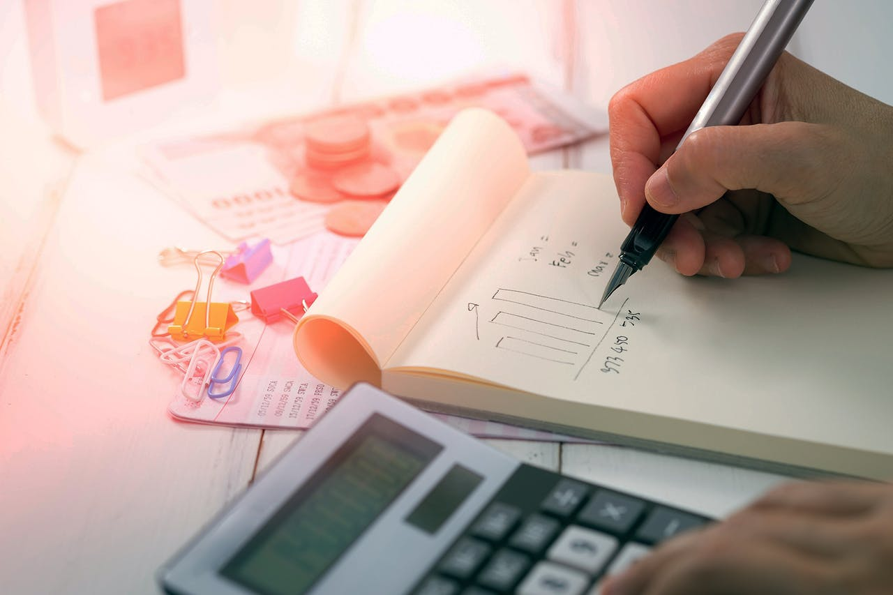 Taschenrechner und Notizbuch zur Berechnung der PKW Abschreibung