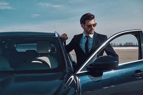 Geschäftsmann steigt in ein Firmenleasing Fahrzeug