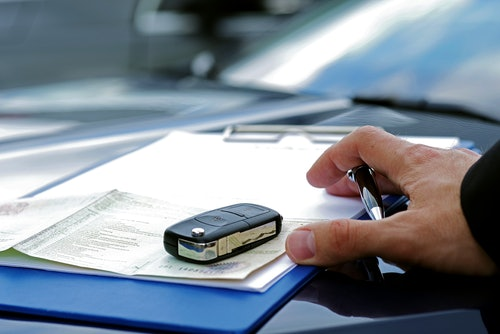 Zulassungsbesceinigung Teil II und Autoschlüssel auf einer Motorhaube