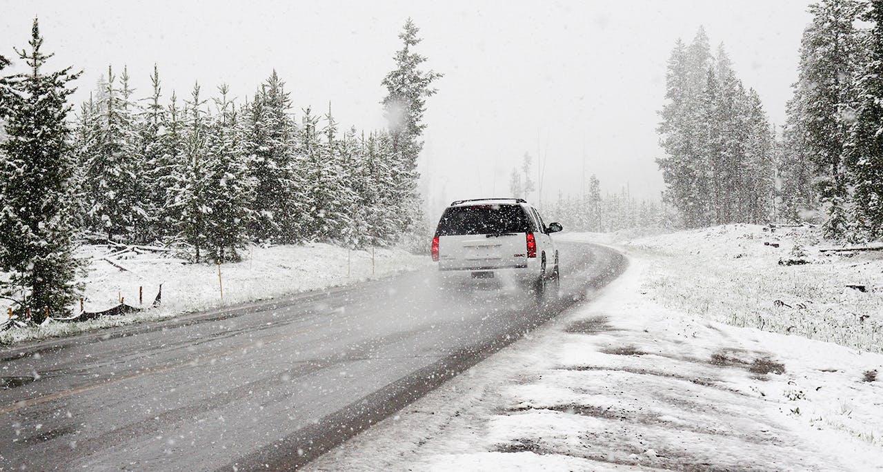 Großer SUV auf Schneebedeckter Straße, fahrend durch Winterwetter