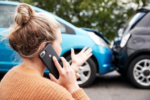 Schaden am Leasingfahrzeug. Aufgebrachte Frau telefoniert im Vordergrund. Welche Versicherungen beim Leasing benötigt werden und wie die bequeme 1-Klick-Versicherung von VEHICULUM funktioniert