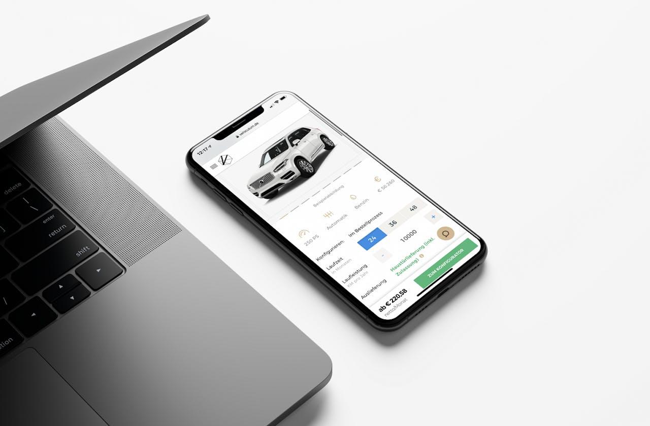VEHICULUM online Leasing Webseite auf dem Smartphone, daneben Laptop auf einem Tisch