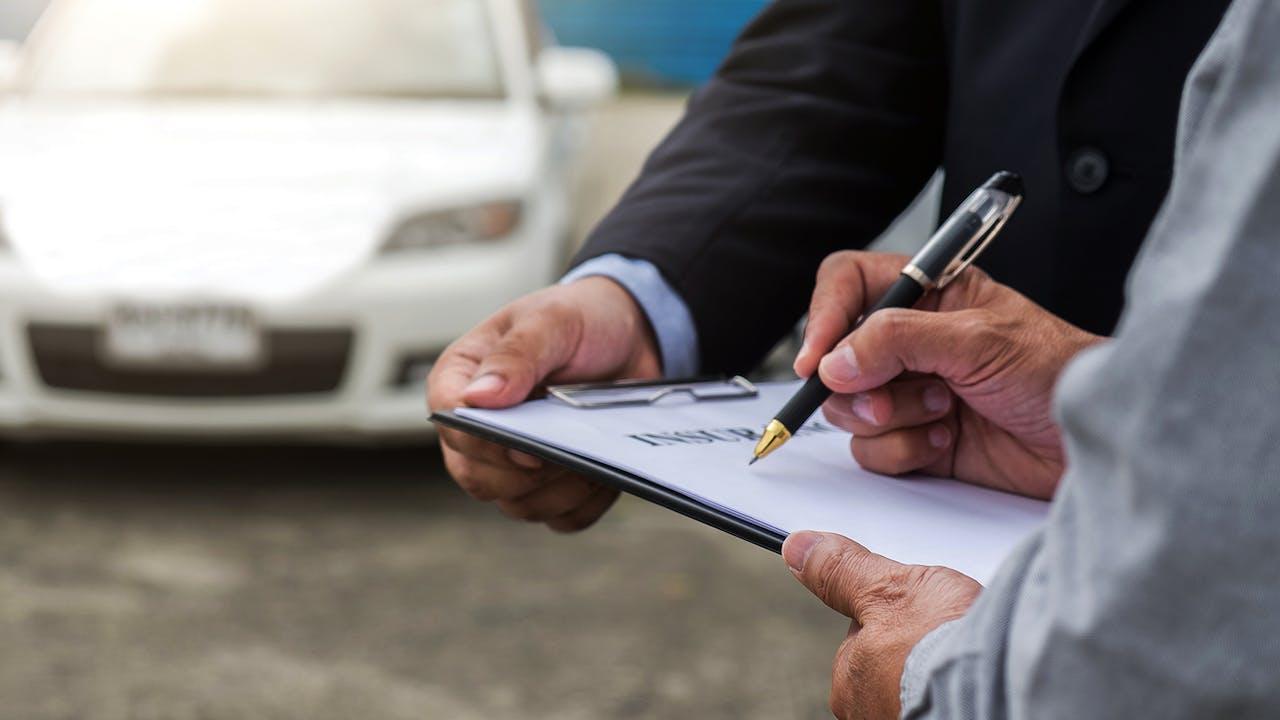 Stichtag Kfz-Versicherung – Ein Mann unterschreibt ein Dokument zum Vertragswechsel