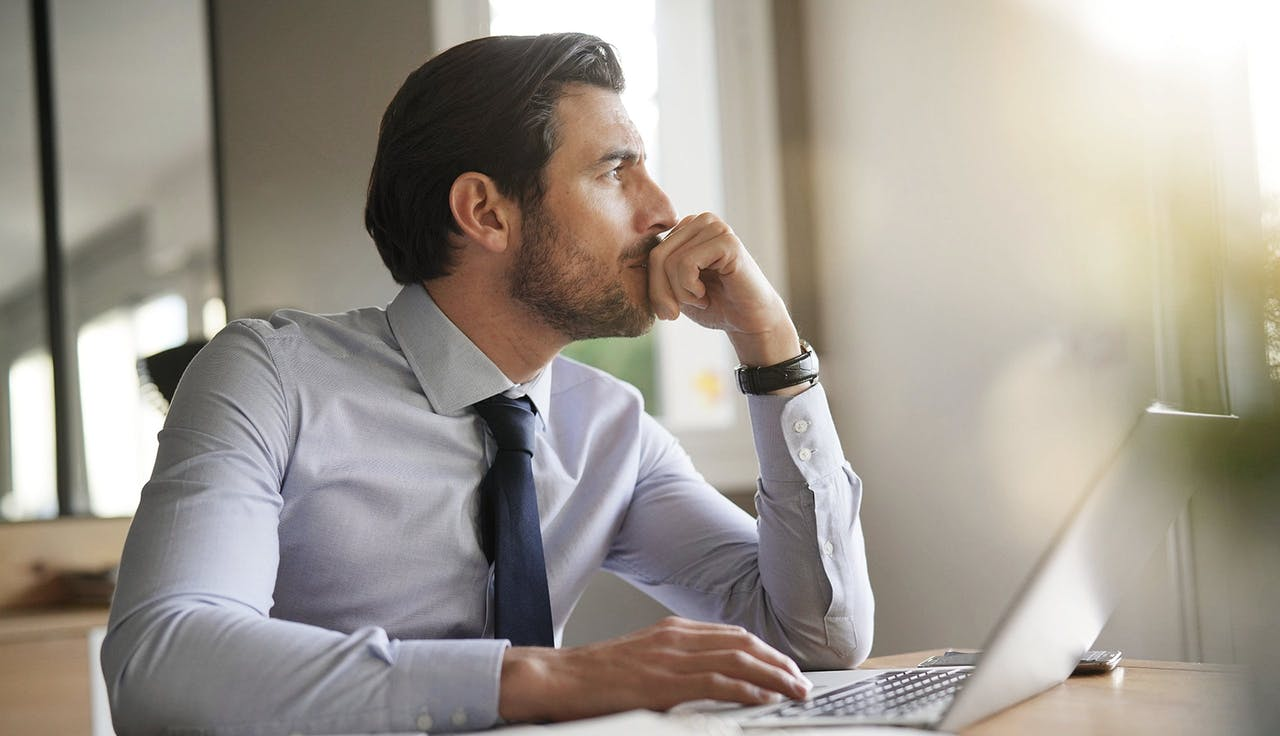 Mann sitzt nachdenklich an einem Schreibtisch
