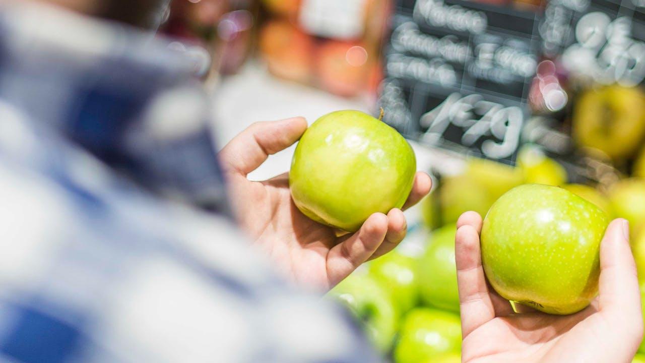 Mensch hält einen Apfel in jeder Hand
