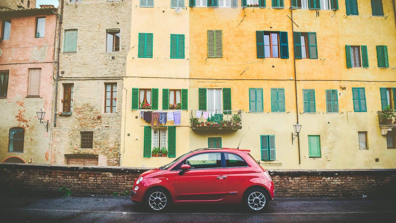 FIAT 500 in Rot, seitliche Aufnahme vor gelber Hauswand