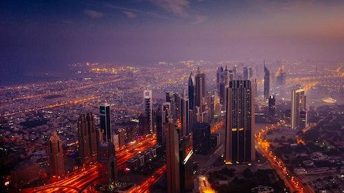 Urbane Mobilität: Elektrofahrzeuge als wichtiger Teil des Modalmixes und nachhaltiger Mobilitätskonzepte, in der Stadt und auf dem Land. Bild: Blick von oben auf eine Stadt in der Dämmerung.