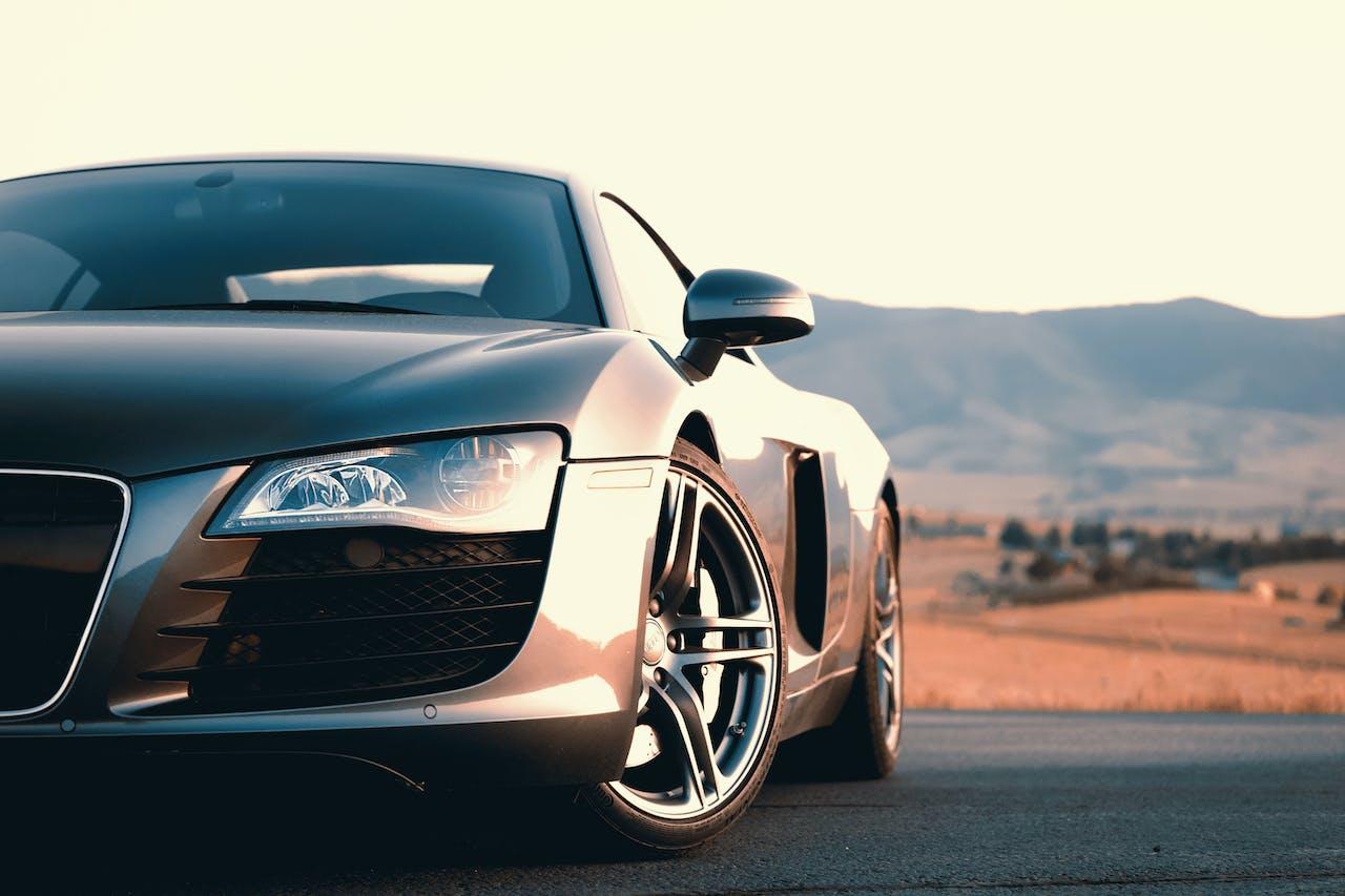 grauer Audi mit bergiger Landschaft im Hintergrund