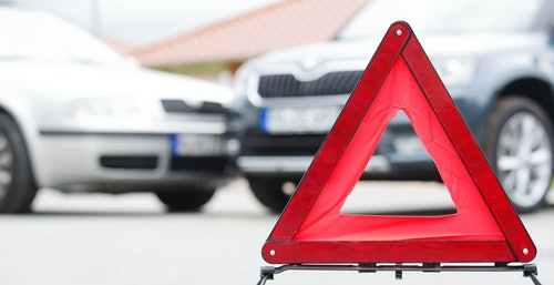 Unfall Leasing Auto mit Warndreieck im Vordergrund