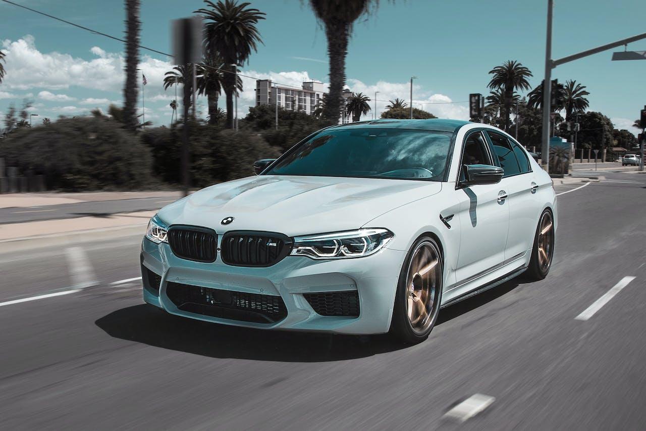 weißer BMW bei der Fahrt auf der Straße