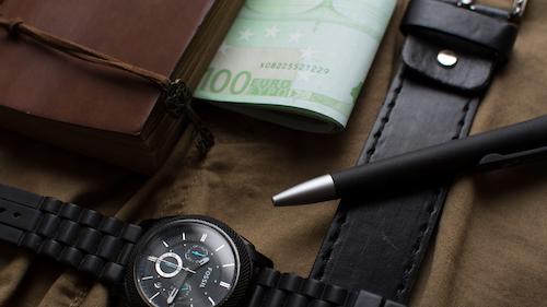 Banner Mehrwertsteuersenkung - Portemonnaie, Geldschein und Armbanduhr auf einer Oberfläche aus Stoff