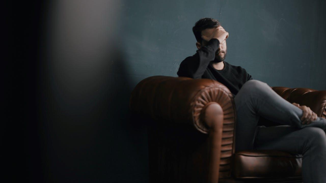 Mann sitzt ängstlich auf einem Sofa
