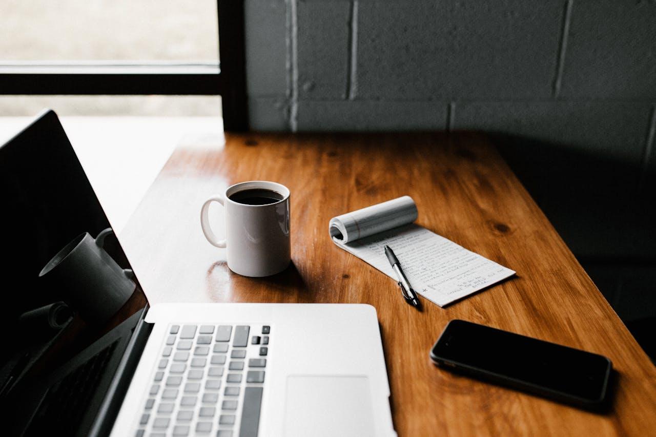 Schreibtisch mit Notebook, Smartphone und Schreibblock. E-Auto Förderungen zu finden ist einfach. VEHICULUM hat die städtischen Förderung für E-Auto Zubehör und Laden zusammengestellt.