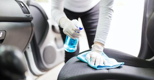 Person reinigt Fahrzeug mit Lappen und Sprühflasche