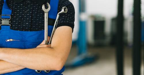 Mechanikerin mit Schraubenschlüsseln in einer Werkstatt