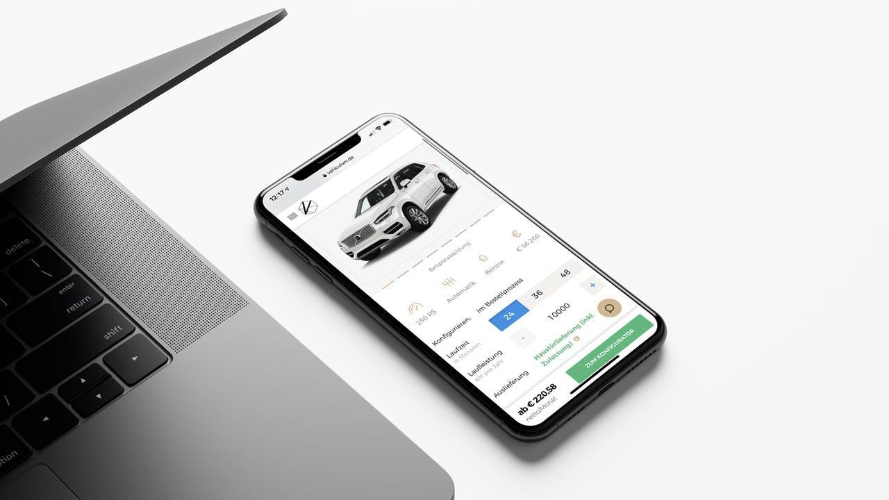 Smartphone neben Laptop. Bildschirm zeigt das VEHICULUM Leasing Angebot eines Volvo XC90. Bei VEHICULUM geht es in nur 10 Minuten zum Leasingvertrag.
