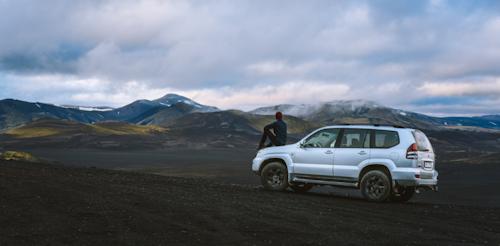 Person auf Motorhaube von Gebraucht-SUV sitzend in weiter Landschaft. Gebrauchtwagen Leasing Ratgeber bei VEHICULUM