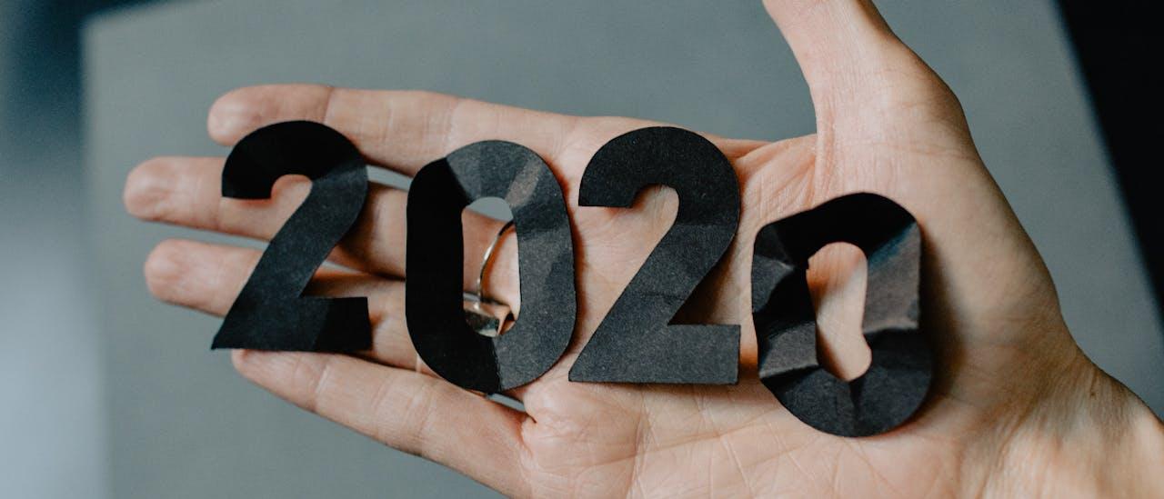 Wort 2020 in schwarzer Schrift ausgeschnitten auf eine Hand gelegt. VEHICULUM Jahresrückblick 2020