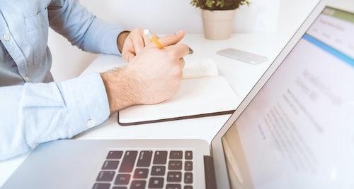Person an Schreibtisch mit Stift in der Hand vor offenem Notizbuch. Im Vordergrund: Laptop. Umweltbonus beantragen
