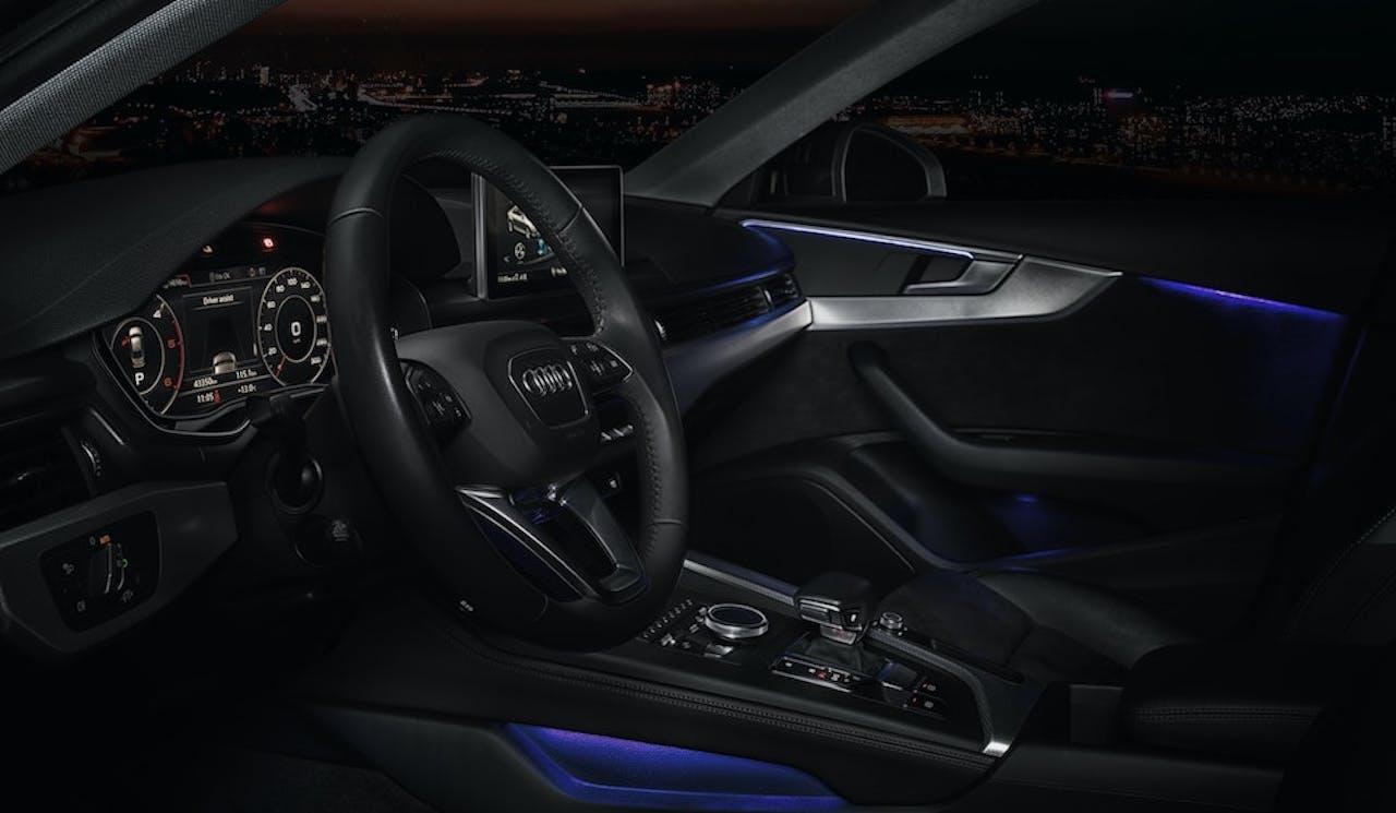 Innenraum eines Audis bei Nacht mit einer Stadt im Hintergrund