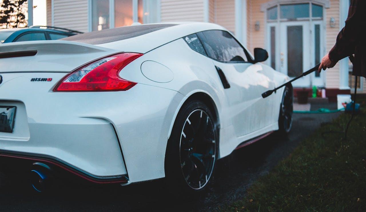 Autopflege für den Lack: Weißer Nissan 370Z Nismo wird mit Hochdruckreiniger vor einem Haus gereinigt