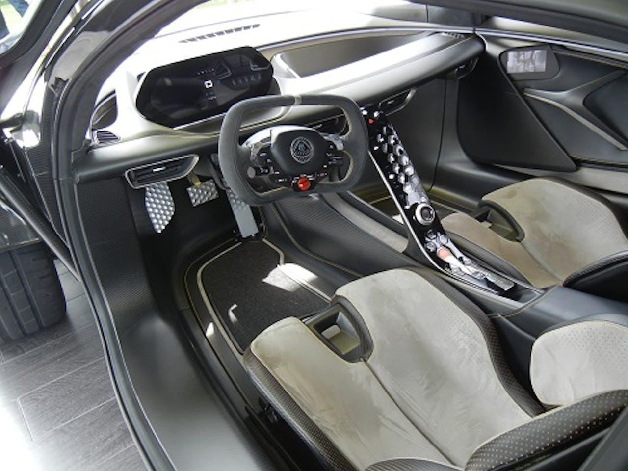 Interieur des Lotus Evija von der Fahrertür aus fotografiert. Leder, Formel-1-Lenkrad und massive Gewichtseinsparung im futuristischen Innenraum