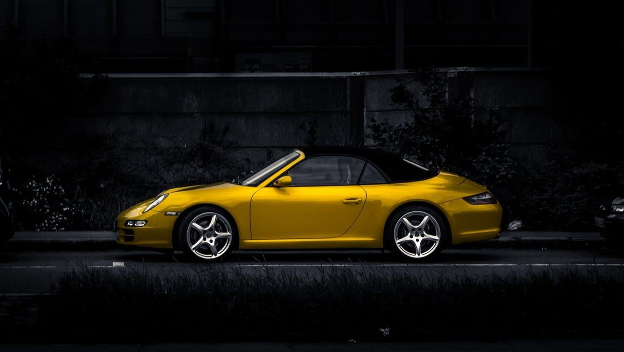 Porsche 911 Cabrio in gelb vor dunklem Hintergrund