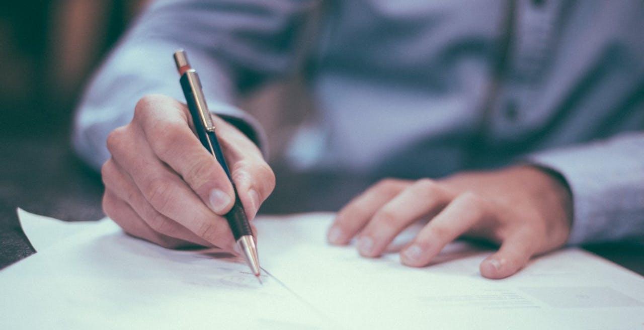 Person mit Stift unterschreibt Vertrag