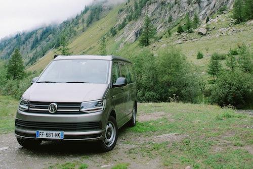 VW T7 als Familienauto in grüner Natur, umgeben von Gebirgen