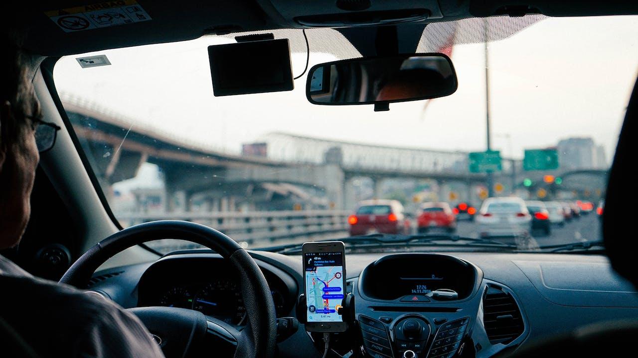 Person am Steuer ihres Leasingfahrzeugs auf der Autobahn