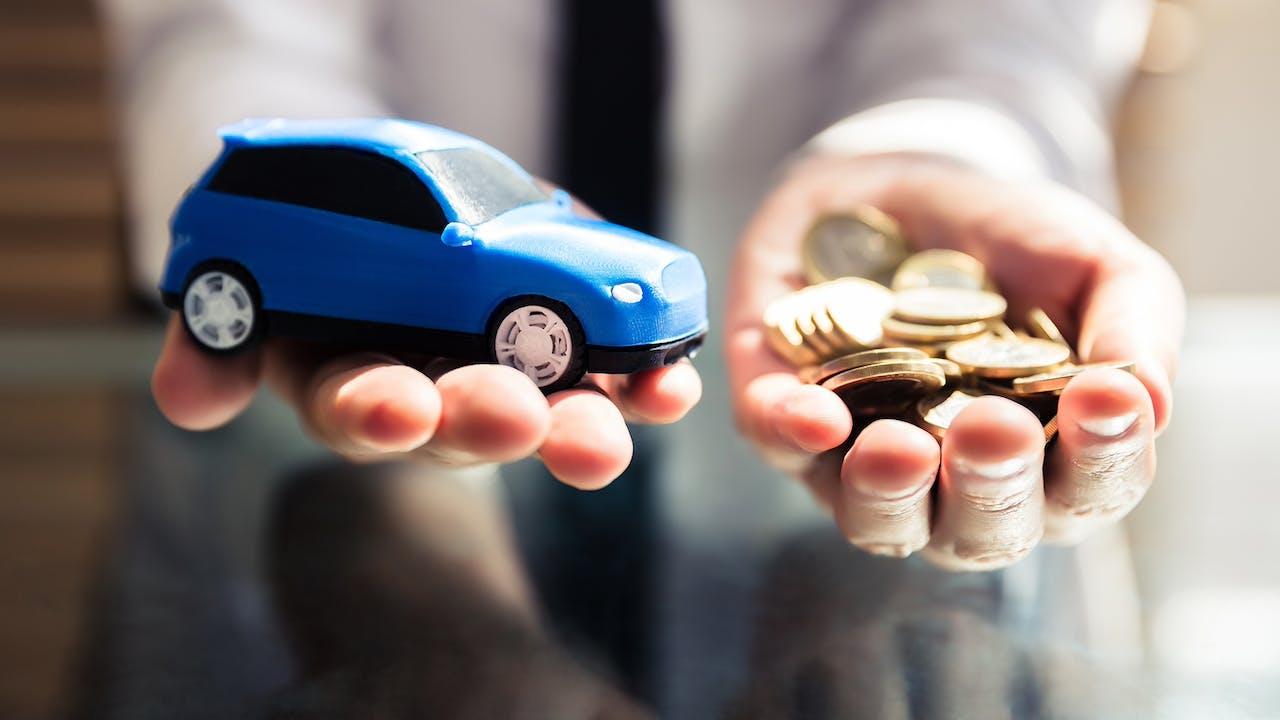 Spielzeugauto in einer Hand, Münzen in einer anderen Hand