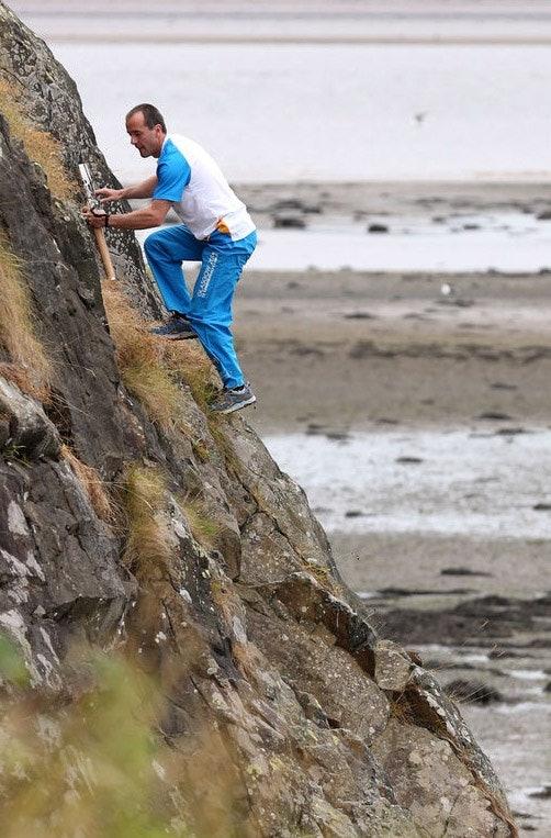 Dave klettert am Dumbarton Rock die Route Plunge. Free solo und mit dem Queens Baton, einem Staffelstab, anlässlich der Commonwealth Games.