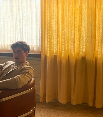man-sit-yellow-curtain