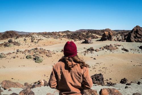 Frau mit roter Mütze guckt auf Vulkanlandschaft