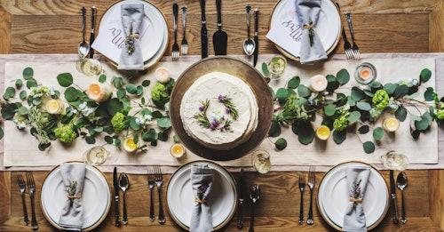 Festlich gedeckter Holztisch mit Kerzen, grünen Zweigen, einer Torte und weißen Tellern.