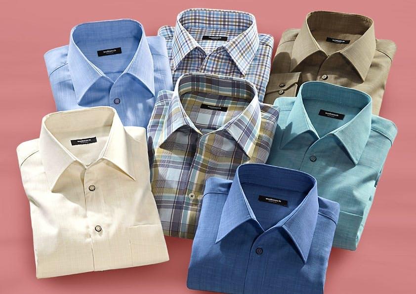 7 Hemden in verschiedenen Farben auf einem lachsfarbenen Hintergrund.
