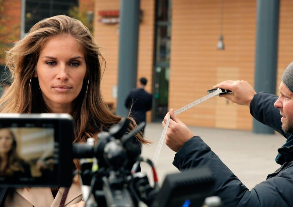 Frau mit braunen Haaren und großen Ohrringen wird gefilmt.