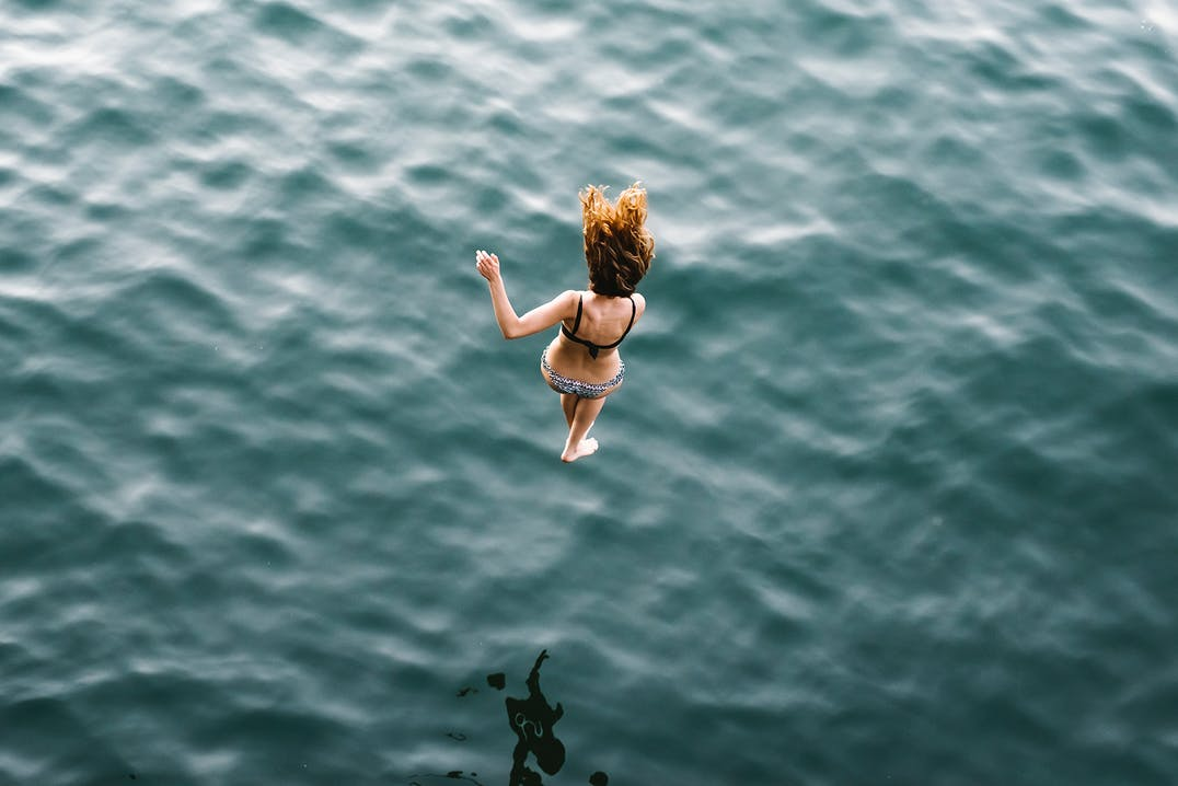 Birds eye view image of a deep blue ocean. Image is captured just as a woman is diving feet first into the ocean.