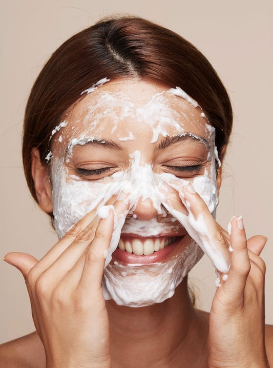 Close up image of a brunette woman smiling while rubbing her face with a foam cleanser.