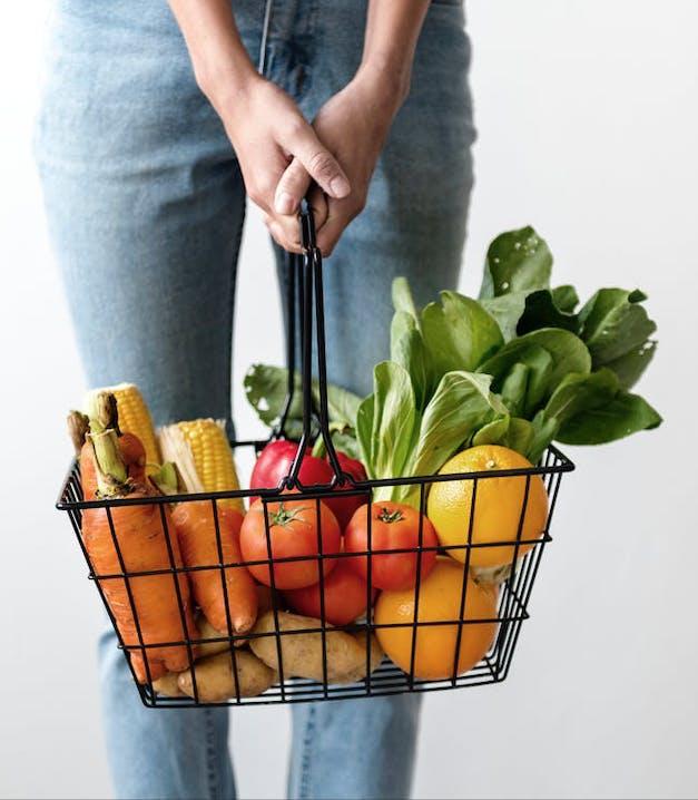 Eine Frau hält einen Korb gefüllt mit frischem Gemüse