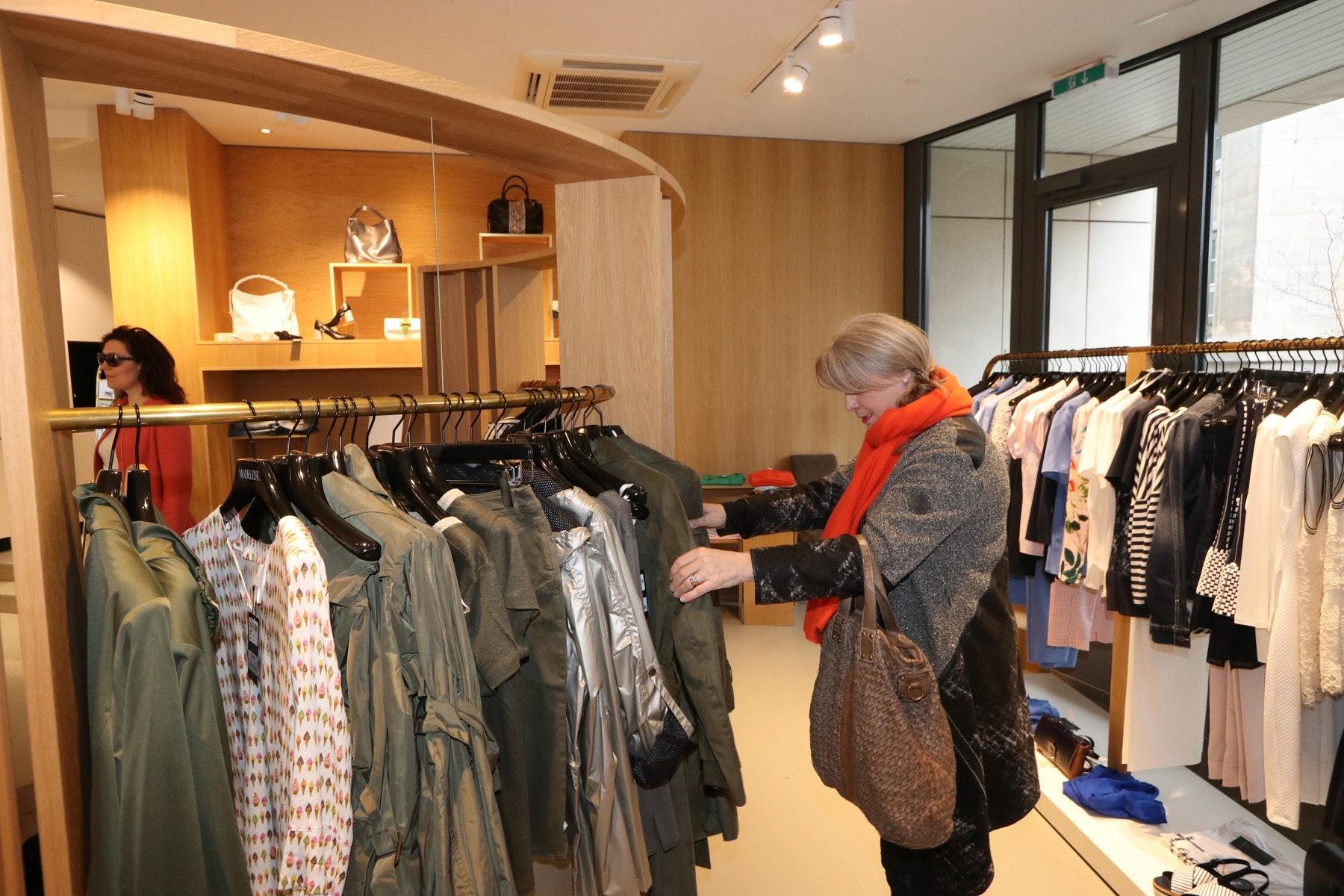 Kundin steht im Bekleidungsgeschäft und sieht sich verschiedene Artikel an, die an der Kleiderstange präsentiert werden.