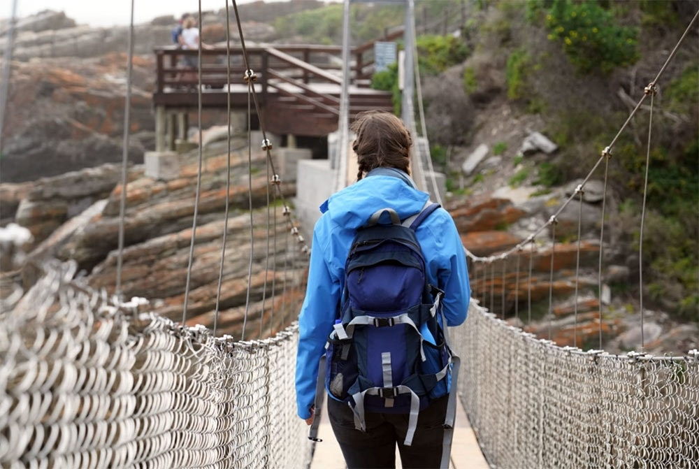 Frau geht über Hängebrücke