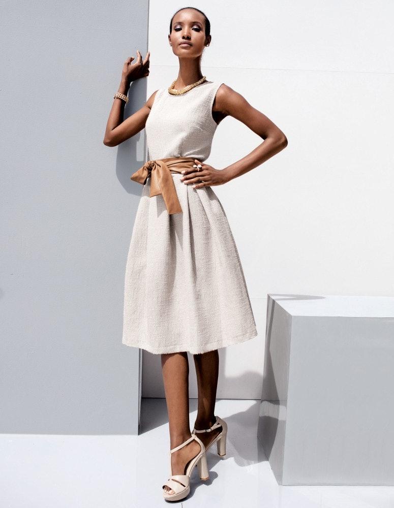 Frau mit Kleid an eine Wand gelehnt.